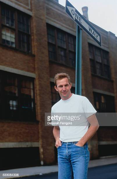 Kevin Costner Standing Under One Way Street Sign