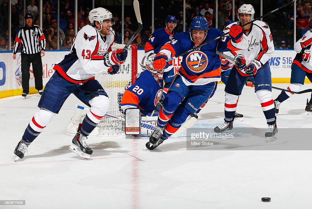 Kevin Czuczman #24 of the New York Islanders pursues the puck against the Washington Capitals at Nassau Veterans Memorial Coliseum on April 5, 2014 in Uniondale, New York. The Capitals defeated the Islanders 4-3.