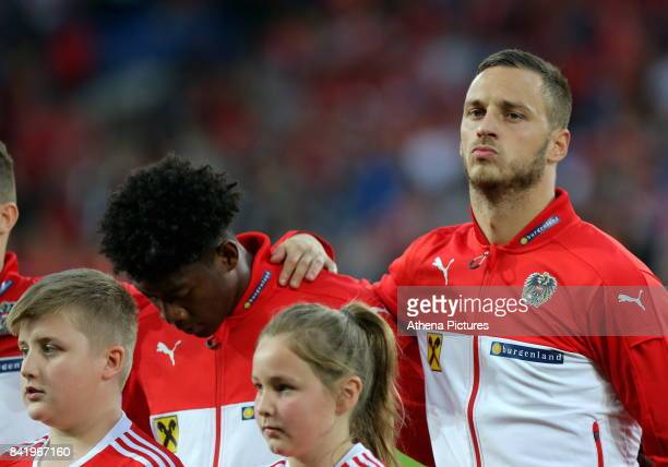Kevin Danso and Marco Arnautovic of Austria stand during their national anthem during the FIFA World Cup Qualifier Group D match between Wales and...