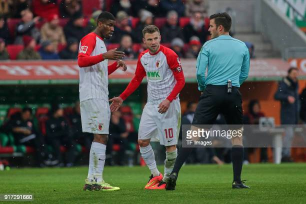 Kevin Danso of Augsburg and Daniel Baier of Augsburg speak with referee Harm Osmers during the Bundesliga match between FC Augsburg and Eintracht...