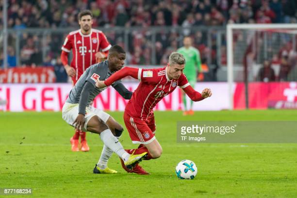 Kevin Danso of Augsburg and Robert Lewandowski of Bayern Muenchen battle for the ball during the Bundesliga match between FC Bayern Muenchen and FC...