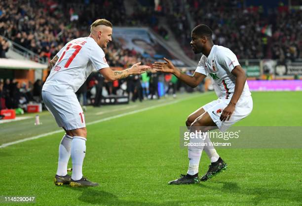 Kevin Danso of Augsburg celebrates after scoring his team's first goal with Jonathan Schmid during the Bundesliga match between FC Augsburg and Bayer...