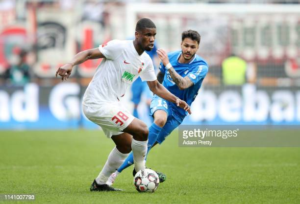 Kevin Danso of Augsburg is challenged by Loureiro Bittencourt of 1899 Hoffenheim during the Bundesliga match between FC Augsburg and TSG 1899...