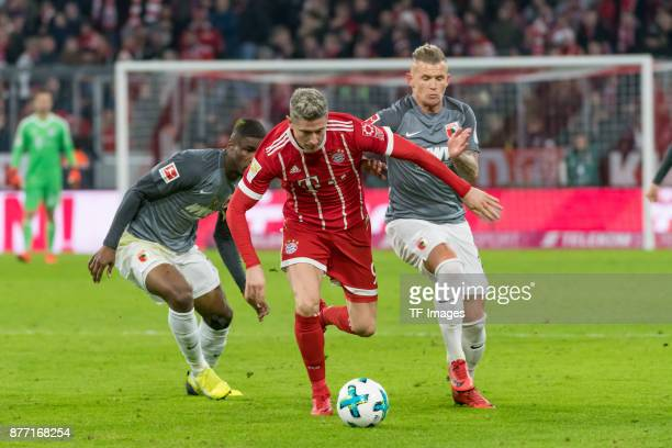 Kevin Danso of Augsburg Robert Lewandowski of Bayern Muenchen and Jonathan Schmid of Augsburg battle for the ball during the Bundesliga match between...