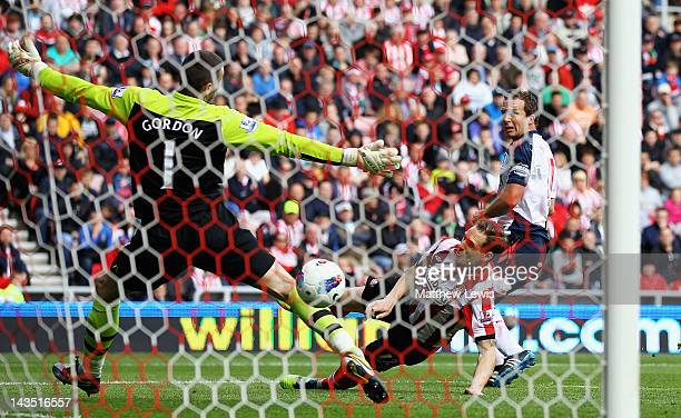 Kevin Davies of Bolton beats the tackle of Matthew Kilgallon of Sunderland to score a goal during the Barclays Premier League match between...
