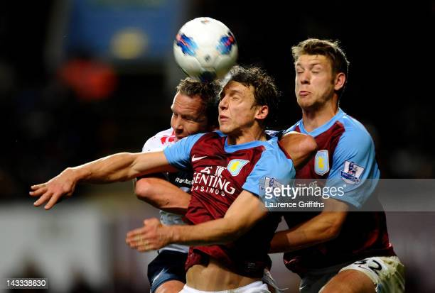 Kevin Davies of Bolton Wanderers goes up for a header with Stephen Warnock and Nathan Baker of Aston Villa the Barclays Premier League match between...