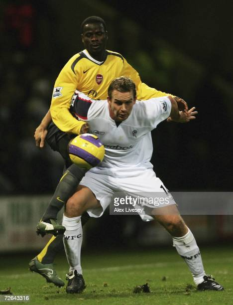 Kevin Davies of Bolton Wanderers holds off a challenge from Emmanuel Eboue of Arsenal during the Barclays Premiership match between Bolton Wanderers...