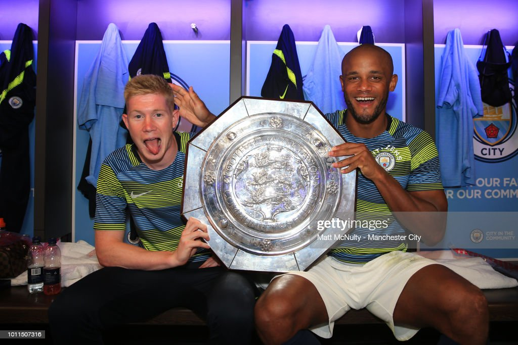 Kevin De Bruyne and Vincent Kompany of Manchester City celebrate with the FA Community Shield Trophy in the dressing room following their sides victory in the FA Community Shield between Manchester City and Chelsea at Wembley Stadium on August 5, 2018 in London, England.