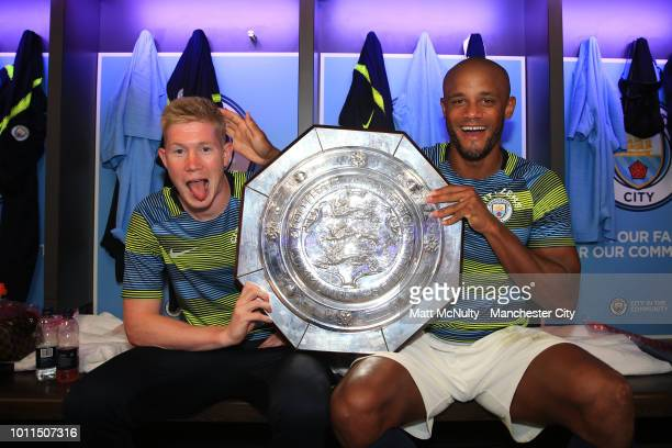 Kevin De Bruyne and Vincent Kompany of Manchester City celebrate with the FA Community Shield Trophy in the dressing room following their sides...