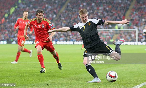 Kevin de Bruyne of Belgium crosses the ball as Joe Allen challenges during the UEFA EURO 2016 qualifying match between Wales and Belgium at the...