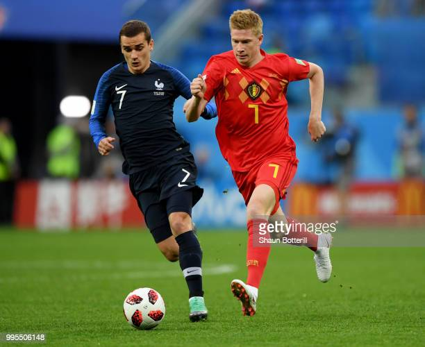 Kevin De Bruyne of Belgium is challenged by Antoine Griezmann of France during the 2018 FIFA World Cup Russia Semi Final match between Belgium and...