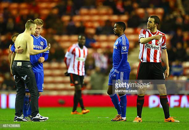 Kevin De Bruyne of Chelsea and John O'Shea of Sunderland reason with a pitch invader as Samuel Eto'o of Chelsea looks on during the Capital One Cup...