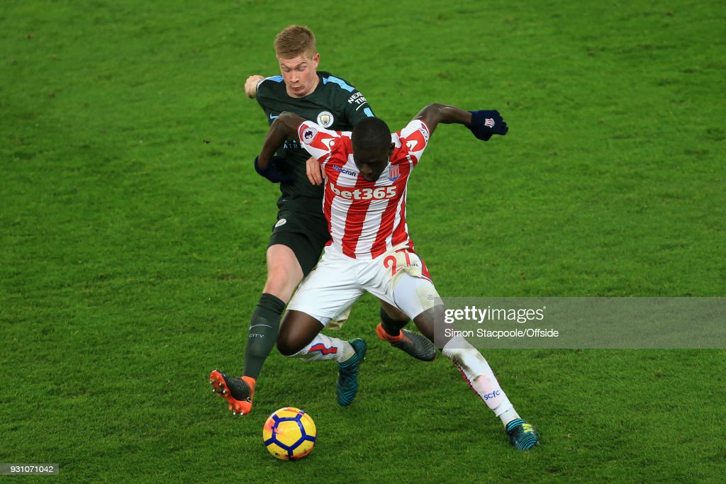Kevin De Bruyne of Man City battles with Papa Alioune Ndiaye of Stoke during the Premier League match between Stoke City and Manchester City at the Bet365 Stadium on March 12, 2018 in Stoke-on-Trent, England.