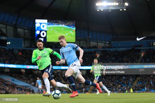 Kevin De Bruyne of Man City battles with Sean Morrison of Cardiff during the Premier League match between Manchester City and Cardiff City at the...
