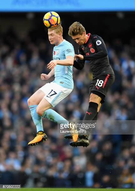 Kevin De Bruyne of Manchester City and Nacho Monreal of Arsenal battle for possession in the air during the Premier League match between Manchester...
