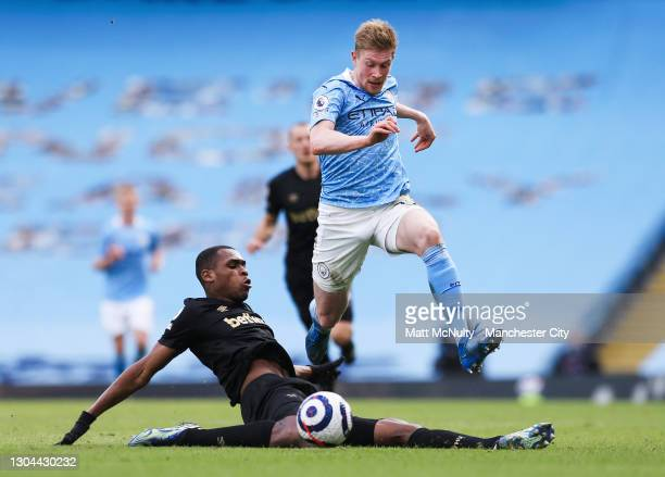 Kevin de Bruyne of Manchester City avoids a tackle by Issa Diop of West Ham during the Premier League match between Manchester City and West Ham...