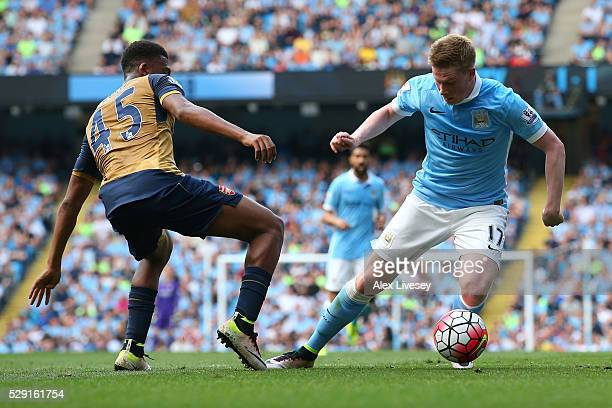 Kevin de Bruyne of Manchester City battles for the ball with Alex Iwobi of Arsenal during the Barclays Premier League match between Manchester City...