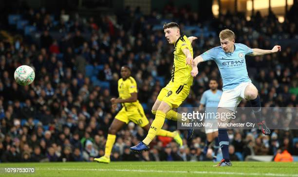 Kevin De Bruyne of Manchester City beats Reece Hutchinson of Burton Albion as he scores his team's first goal during the Carabao Cup Semi Final First...