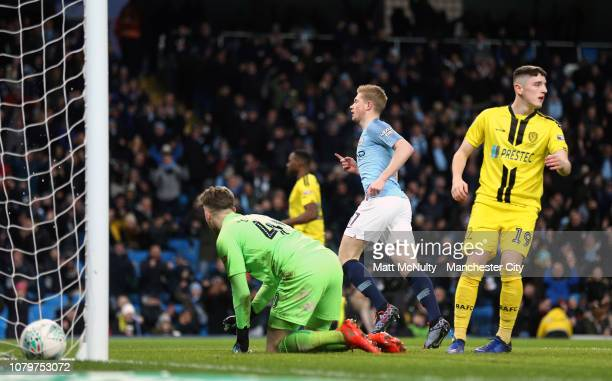 Kevin De Bruyne of Manchester City celebrates after scoring his team's first goal as Bradley Collins and Reece Hutchinson of Burton Albion react...