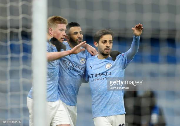 Kevin De Bruyne of Manchester City celebrates with teammates Riyad Mahrez and Bernardo Silva after scoring their team's first goal during the UEFA...