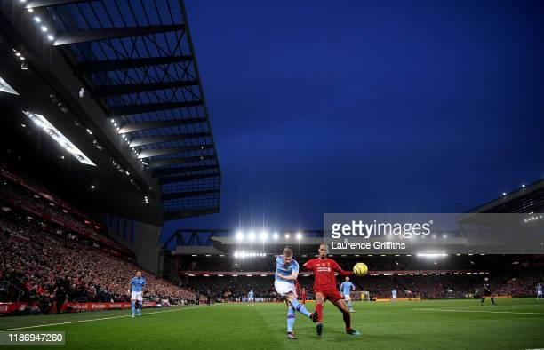 Kevin De Bruyne of Manchester City crosses the ball under pressure from Fabinho of Liverpool during the Premier League match between Liverpool FC and...