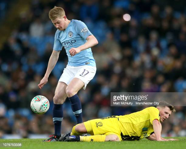 Kevin De Bruyne of Manchester City evades Jamie Allen of Burton Albion during the Carabao Cup Semi Final First Leg match between Manchester City and...