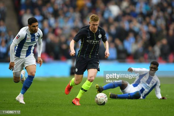 Kevin De Bruyne of Manchester City gets past Yves Bissouma and Alireza Jahanbakhsh of Brighton Hove Albion during the FA Cup Semi Final match between...