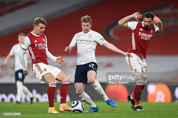 Kevin De Bruyne of Manchester City in action with Martin Odegaard of Arsenal during the Premier League match between Arsenal and Manchester City at...