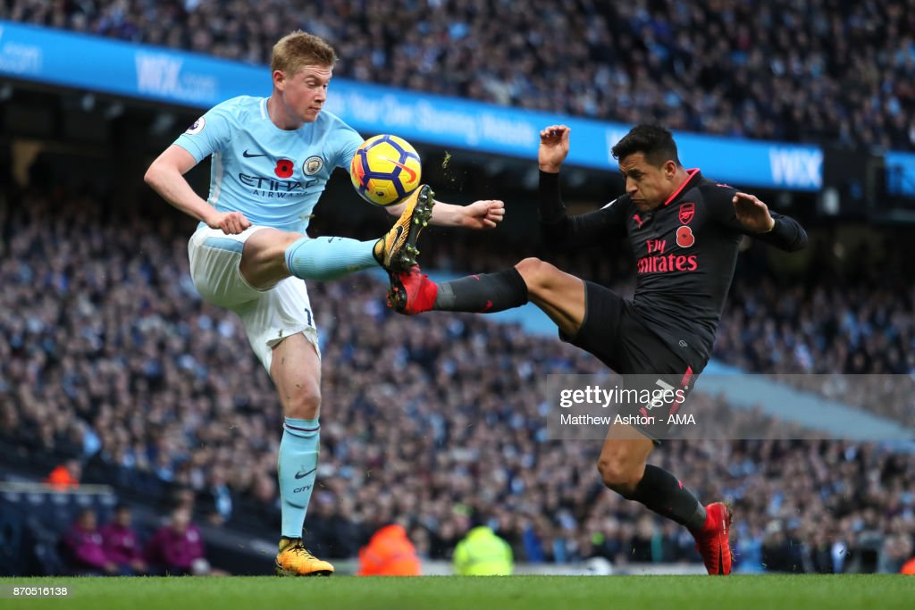 Kevin de Bruyne of Manchester City is challenged by Alexis Sanchez of Arsenal during the Premier League match between Manchester City and Arsenal at Etihad Stadium on November 5, 2017 in Manchester, England.
