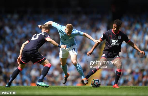 Kevin De Bruyne of Manchester City is challenged by Florent Hadergjonaj of Huddersfield Town and Steve Mounie of Huddersfield Town during the Premier...