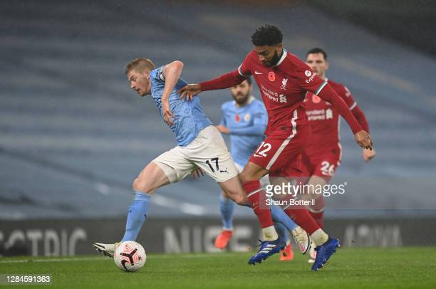 Kevin De Bruyne of Manchester City is challenged by Joe Gomez of Liverpool during the Premier League match between Manchester City and Liverpool at...