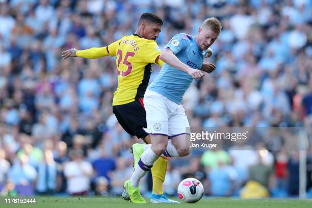Kevin De Bruyne of Manchester City is challenged by Jose Holebas of Watford during the Premier League match between Manchester City and Watford FC at...
