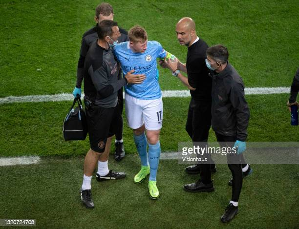 Kevin De Bruyne of Manchester City is consoled by manager Josep Guardiola after he is substituted after receiving a head injury during the UEFA...