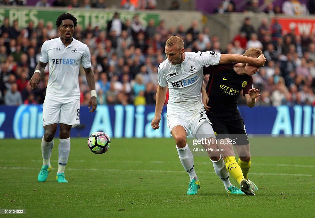 Kevin De Bruyne of Manchester City (R) is fouled by Mike van der Hoorn of Swansea City (C) for which a penalty kick was awarded during the Premier League match between Swansea City and Manchester City at The Liberty Stadium on September 24, 2016 in Swansea, Wales.