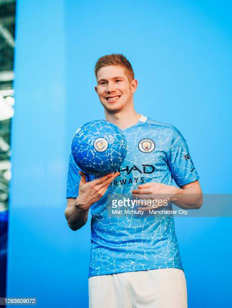 Kevin de Bruyne of Manchester City poses wearing the 2020/21 Puma home jersey at the City Football Academy on August 03, 2020 in Manchester, England.