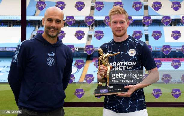 Kevin De Bruyne of Manchester City receives the Playmaker Award from Pep Guardiola, Manager of Manchester City after the Premier League match between...