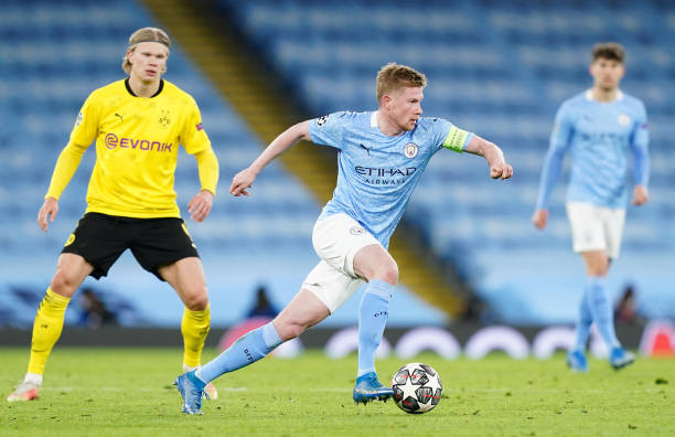 Kevin De Bruyne of Manchester City runs with the ball as Erling Haaland of Borussia Dortmund looks on during the UEFA Champions League Quarter Final...