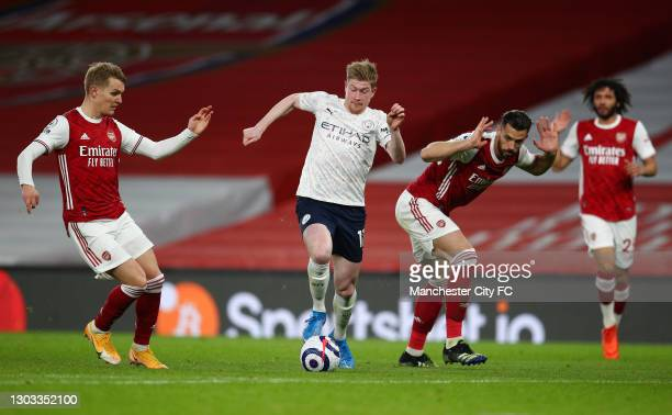 Kevin De Bruyne of Manchester City runs with the ball whilst under pressure from Martin Odegaard and Pablo Mari of Arsenal during the Premier League...