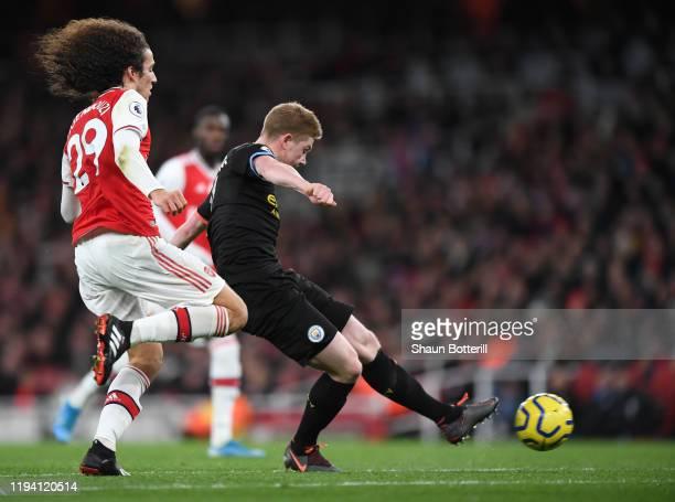 Kevin De Bruyne of Manchester City scores his team's third goal while under pressure from Matteo Guendouzi of Arsenal during the Premier League match...