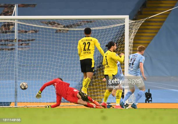 Kevin De Bruyne of Manchester City scores their team's first goal under pressure from Emre Can of Borussia Dortmund during the UEFA Champions League...