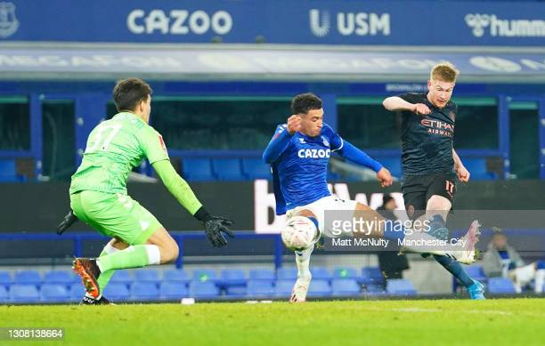 Kevin De Bruyne of Manchester City scores their team's second goal under pressure from Ben Godfrey and Joao Virginia of Everton during The Emirates...