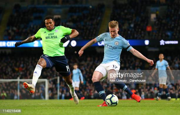 Kevin De Bruyne of Manchester City shoots ahead of Nathaniel MendezLaing of Cardiff City during the Premier League match between Manchester City and...