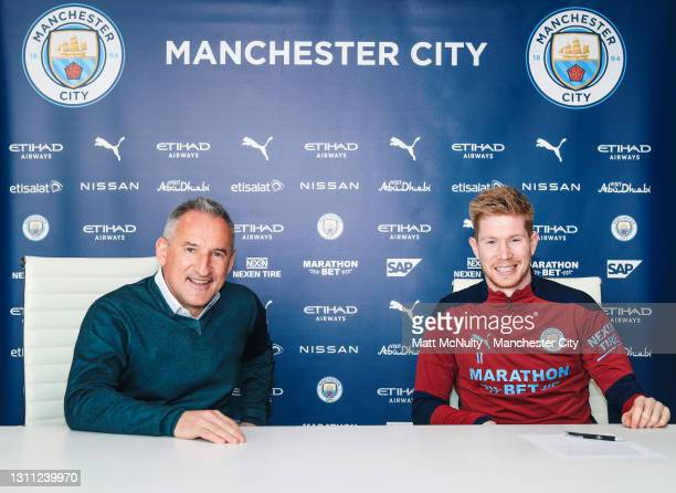 Kevin de Bruyne of Manchester City signs a new contract extension at the club alongside Txiki Begiristain, Director of Football at Manchester City...