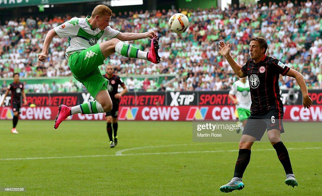 Kevin De Bruyne of VfL Wolfsburg jumps for the ball next to Bastian Oczipka of Eintracht Frankfurt during the Bundesliga match between VfL Wolfsburg and Eintracht Frankfurt at Volkswagen Arena on August 16, 2015 in Wolfsburg, Germany.