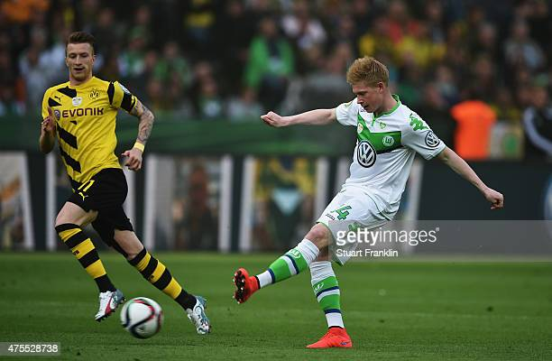 Kevin De Bruyne of Wolfsburg is challenged by Marco Reus of Dortmund during the DFB Cup Final between Borussia Dortmund and VfL Wolfsburg at...