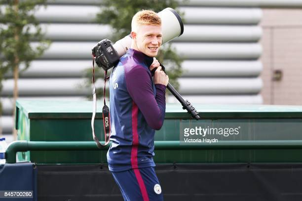 Kevin De Bruyne walks off with a camera before training at Manchester City Football Academy on September 11 2017 in Manchester England