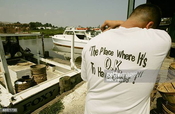 Kevin Doane wearing a shirt that reads The Place Where It's OK To Get Crabs wipes his brow while unloading freshly caught Maryland Blur Crabs aboard...