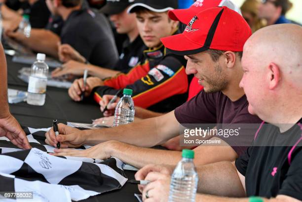 Kevin Donahue Chevrolet Silverado signs a flag during the driver autograph session before the start of the NASCAR Camping World Truck Series Drivin'...