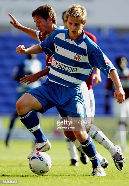 Kevin Doyle of Reading ia tackled by John Harley of Burnley during the CocaCola Championship match between Reading FC and Burnley FC at the Madejski...