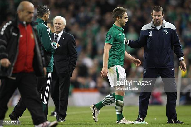 Kevin Doyle of Republic of Ireland walks off the pitch after being sent off aided by Alan Kelly the Ireland goalkeepoing coach as Giovanni Trapattoni...